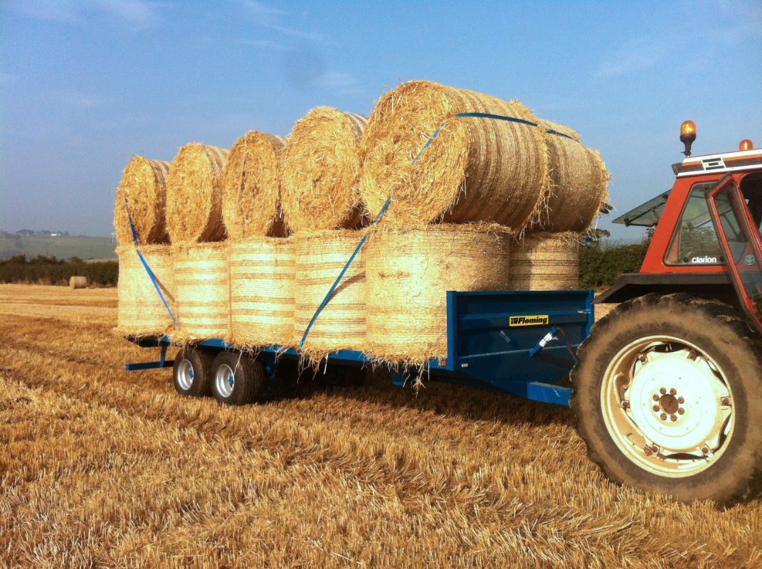 flatbed bale trailer loaded with round straw bales